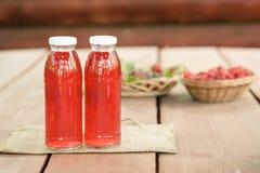 Twee flessen koude gestoofd fruit van geassorteerde bessen Stock Afbeeldingen