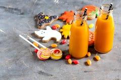 Twee flessen pompoensap met het zwarte voedsel van Halloween van de stro Horizontale foto en snoepjesconcept Stock Afbeelding