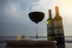 Twee flessen rode Franse wijn met wijnglas en kaas; stock foto's