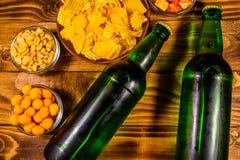 Twee flessen van bier en verschillende snacks op houten lijst Hoogste mening stock foto
