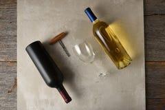 Twee flessen wijn op een grijze tegeloppervlakte op een rustieke houten lijst, witte wijn en rode wijn stock foto's