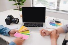 Twee fotografen met camera en laptop computer die in bureau werken stock fotografie