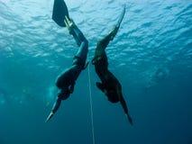 Twee freedivers maken gelijktijdig in Gat duiken Bue royalty-vrije stock afbeeldingen