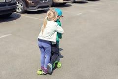 Twee frinedsjongen en meisje die pret hebben die één autoped samen gelijktijdig berijden Kinderen die op de weg van het autoparke stock fotografie