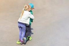 Twee frinedsjongen en meisje die pret hebben die één autoped samen gelijktijdig berijden Kinderensiblings, broer en zuster royalty-vrije stock fotografie