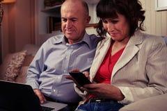 Twee geamuseerde mensen die met hun apparaten spelen Stock Afbeelding