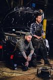 Twee gebaarde getatoeeerde werktuigkundigen dichtbij de auto in een workshop stock afbeeldingen