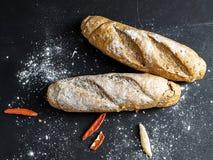 Twee gebakken brood met bloem en koele peper op een zwarte bordachtergrond royalty-vrije stock afbeelding