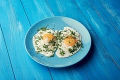 Twee gebraden eieren voor gezond ontbijt in blauwe plaat op blauwe houten lijst royalty-vrije stock fotografie