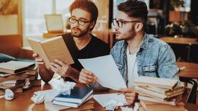 Twee Geconcentreerde Tekstschrijvers die binnen samenwerken stock fotografie