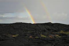 Twee gedeeltelijke Regenbogen en zwarte lava Stock Afbeelding