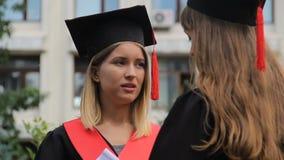 Twee gediplomeerde studenten die zich dichtbij universitair bevinden en over toekomstige carrière spreken stock footage