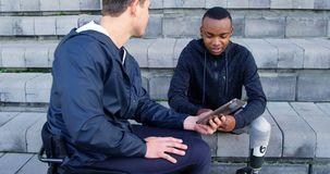 Twee gehandicapte atletiek die over digitale tablet 4k bespreken stock footage