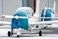 Twee gehulde kleine sportenvliegtuigen naast aan de hangaars Royalty-vrije Stock Fotografie