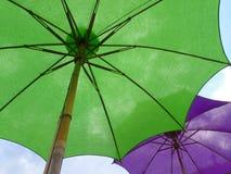 Twee gekleurd trillend parasols, één groen en één purple tegen zonnige blauwe hemel stock afbeeldingen