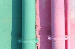 twee gekleurde goten op de geschilderde muur van het huis stock afbeelding