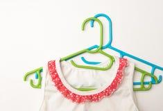 Twee gekleurde hangers en een babykleding op een monophonic achtergrond Royalty-vrije Stock Afbeelding