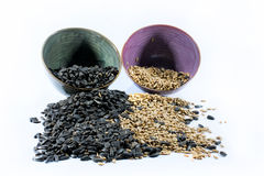 Twee gekleurde koppen met zwarte zaden en gepelde zaden Stock Foto's