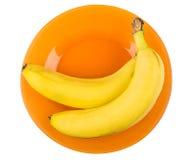 Twee gele bananen in oranje die plaat op wit wordt geïsoleerd Stock Foto