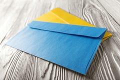 Twee gele en blauwe enveloppen met brieven op witte houten achtergrond Spaties voor de ontwerper Concepten, ideeën voor post stock fotografie