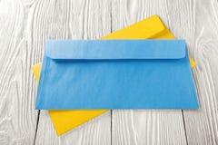 Twee gele en blauwe enveloppen met brieven op witte houten achtergrond Spaties voor de ontwerper Concepten, ideeën voor post royalty-vrije stock foto's