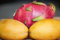 Twee gele rijpe mango's en een draakfruit Royalty-vrije Stock Afbeelding
