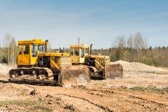 Twee gele vuile oude bulldozertribune op een bouwwerf op een zonnige dag tegen een achtergrond van blauwe hemel Royalty-vrije Stock Fotografie