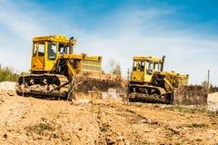 Twee gele vuile oude bulldozertribune op een bouwwerf op een zonnige dag tegen een achtergrond van blauwe hemel Stock Foto's