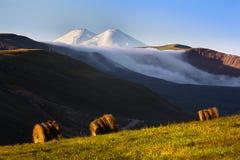 Twee-geleide die Elbrus door de ochtendzon wordt aangestoken royalty-vrije stock foto's