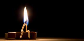 Twee gelijken branden die samen op het lucifersdoosje in dark zitten Stock Afbeeldingen