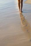 Twee gelooide vrouwenbenen die op zandstrand lopen Royalty-vrije Stock Foto