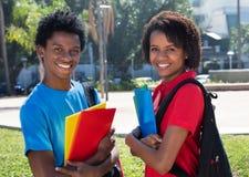 Twee gelukkige Afrikaanse Amerikaanse studenten op campus van universiteit Stock Afbeelding