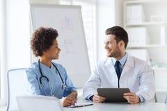 Twee gelukkige artsen die op het ziekenhuiskantoor samenkomen Royalty-vrije Stock Afbeelding