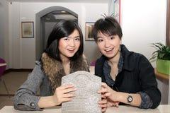 Twee gelukkige Aziatische meisjes die in koffie zitten Stock Fotografie