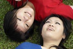 Twee gelukkige Aziatische meisjes op gras Royalty-vrije Stock Afbeelding