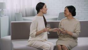 Twee gelukkige Aziatische vrouwen die witte wijn, viering drinken van overwinning, vennootschap stock video