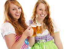 Twee gelukkige Beierse meisjes met bier Royalty-vrije Stock Afbeeldingen