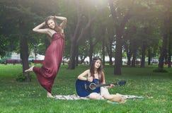 Twee gelukkige boho elegante modieuze meisjes met gitaar, picknick Stock Foto's