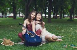 Twee gelukkige boho elegante modieuze meisjes met gitaar, picknick Royalty-vrije Stock Foto's