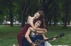 Twee gelukkige boho elegante modieuze meisjes met gitaar, picknick Stock Fotografie