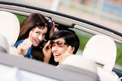 Twee gelukkige in de auto zitten en meisjes die omhoog beduimelen royalty-vrije stock fotografie