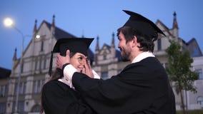 Twee gelukkige een diploma behalende studenten De mannelijke gediplomeerde student helpt het meisje om GLB recht te maken Zij gli stock videobeelden