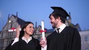 Twee gelukkige een diploma behalende studenten die aan camera stellen die hun diploma's tonen De wind blaast GLB van meisjeshoofd stock footage