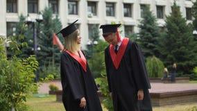 Twee gelukkige gediplomeerden die in park dichtbij universitair ontspannen en over toekomst spreken stock videobeelden