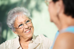 Twee gelukkige hogere vrouwen die in park spreken Stock Foto's