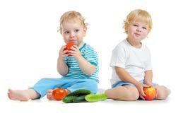 Twee gelukkige jonge geitjes die gezonde voedselvruchten en groenten eten Stock Foto