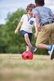 Twee gelukkige jonge geitjes die voetbal spelen Royalty-vrije Stock Foto's