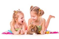 Twee gelukkige jonge geitjes met Pasen konijntje en eieren. Gelukkige Pasen stock foto