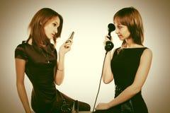 Twee gelukkige jonge maniervrouwen met mobiele en retro telefoon Royalty-vrije Stock Afbeeldingen