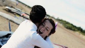 Twee gelukkige jonge meisjes die op strandglimlach in camera dansen Zonnige dag omhels stock footage